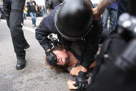 FOTOGALERIA: Un agente intenta desalojar a un joven 'indignado' del 'Movimiento 15-M' en Barcelona