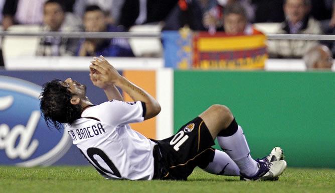 El centrocampista argentino del Valencia C.F. Éver Banega cae al suelo lesionado durante el partido correspondiente a la cuarta jornada de la Fase de grupos de la Liga de Campeones contra el Bayer Leverkusen