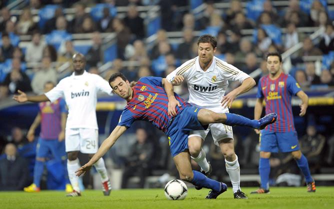 El centrocampista del F. C. Barcelona, Sergio Busquets , cae ante la entrada del jugador del Real Madrid, Xavi Alonso, durante el encuentro correspondiente a la ida de los cuartos de final de la Copa del Rey, que ambos equipos disputan esta noche en el estadio Santiago Bernabeu, en Madrid