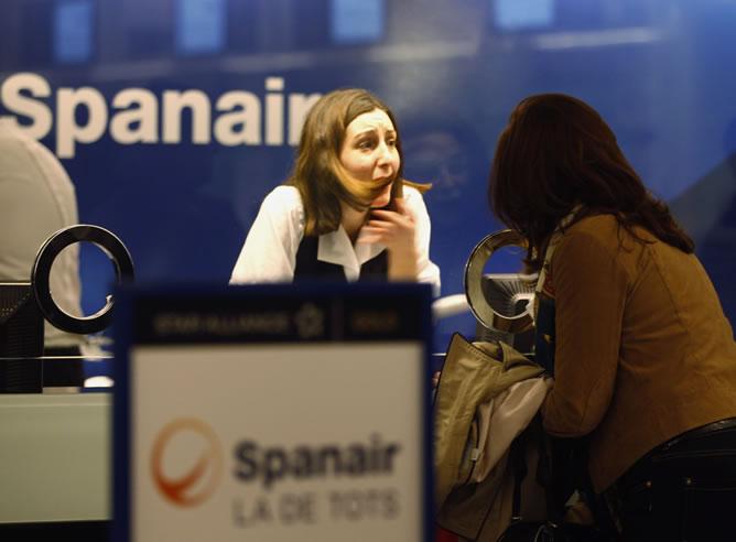 Una trabajadora de Spanair atiende a una afectada por la cancelación de su vuelo