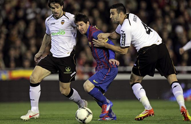 El delantero argentino del Barcelona Lionel Messi intenta superar a los jugadores del Valencia Davi Albelda  y Adil Rami durante el partido correspondiente a la ida de las semifinales de la Copa del Rey