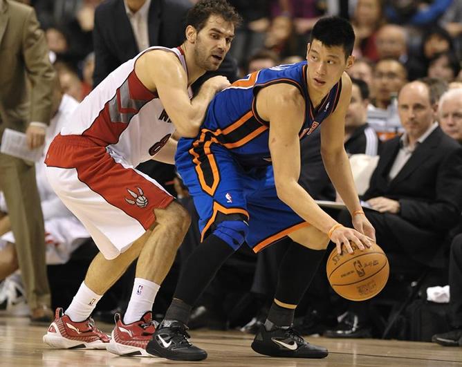 El jugador de los Knicks de Nueva York Jeremy Lin controla la bola ante el español José Calderón, de los Raptors de Toronto