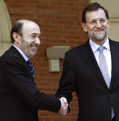 El jefe del Ejecutivo, Mariano Rajoy, y el líder del PSOE, Alfredo Pérez Rubalaba, se saludan antes de posar unos segundos ante los fotógrafos en la escalinata del Palacio de La Moncloa