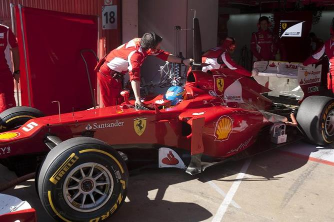 El piloto español de Ferrari Fernando Alonso es ayudado por sus mecánicos durante la segunda jornada de entrenamientos que se realizan en el Circuit de Catalunya, en Montmeló, dentro de los ensayos de los equipos que disputarán el Mundial de Fórmula Uno de 2012.