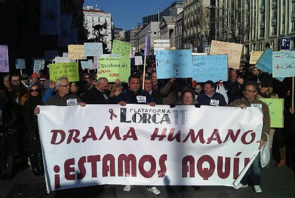 """Vecinos de Lorca se manifiestan en Madrid con una pancarta con el lema """"¡Estamos aquí!"""" dirigido a los políticos, a los que acusan de haberse olvidado de sus necesidades"""
