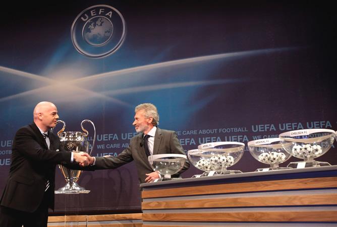 El secretario general de la UEFA saluda a Paul Breitner, embajador de la final de Munich, encargado del sorteo de la Liga de Campeones