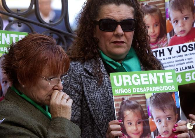 Dos mujeres portan carteles con fotografías de los niños onubenses Ruth y José Ortiz