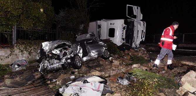 Estado en el que ha quedado el vehículo que ha colisionado esta noche con un camión (al fondo) en el termino municipal de Sorauren, en Pamplona, donde tres personas han sido sacadas del coche por los bomberos.