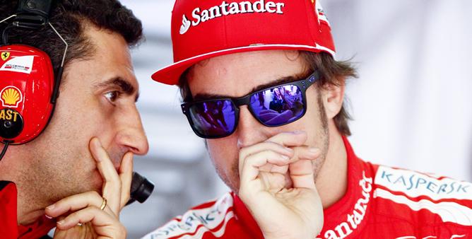 El piloto español de Fórmula Uno de la escudería Ferrari, Fernando Alonso (dcha), conversa con un miembro del equipo en el garage, durante la tercera y última sesión de entrenamientos libres para el Gran Premio de China que se disputa en Shanghái
