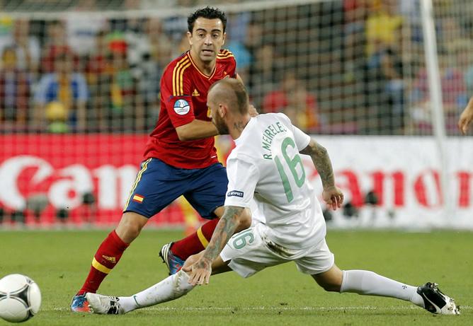 El centrocampista de la selección española Xavi Hernández pelea un balón con el centrocampista de Portugal Raúl Meireles, correspondiente a la primera semifinal de la Eurocopa 2012, esta noche en el estadio Donbass Arena de Donetsk