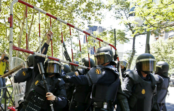 Agentes antidisturbios detienen una valla lanzada por participantes en la manifestación que se desarrolló hoy en Madrid en apoyo de la minería del carbón