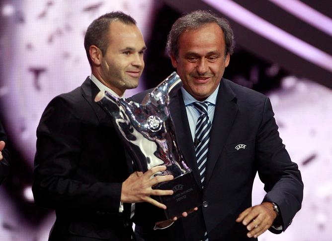 El centrocampista español Andrés Iniesta recibe de manos del presidente de la UEFA, Michel Platini, el Premio UEFA al Mejor Jugador de la campaña 2011/12.