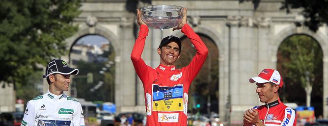 El ciclista español del Saxo Bank Alberto Contador levanta el trofeo de campeón en presencia del segundo clasificado, Alejandro Valverde, del Movistar y del tercero, Joaquim Rodriguez, del Katusha tras la etapa final de la 67 edición de la Vuelta a España de ciclismo celebrada hoy 9 septiembre de 2012 entre Cercedilla y Madrid.