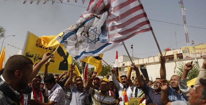 Varios manifestantes queman banderas israelíes y estadounidenses durante una protesta en Basra, la segunda ciudad de Irak
