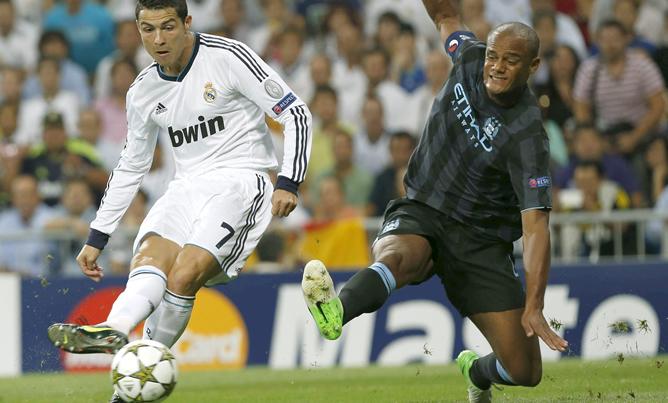 El jugador portugués del Real Madrid Cristiano Ronaldo trata de disparar ante la oposición del defensa belga del Manchester City Vincent Kompany durante el partido de la Liga de Campeones