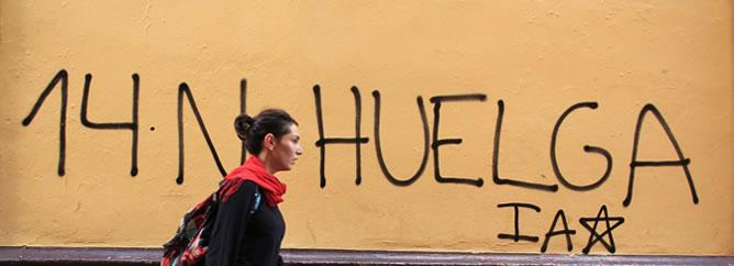 Una joven camina por una calle de Sevilla en la que se ve una pintada de la huelga general