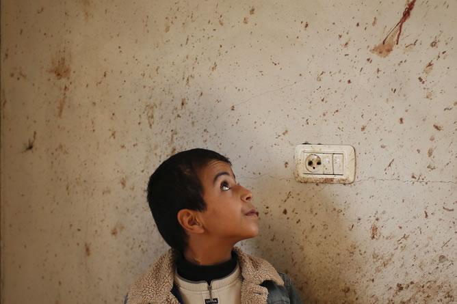 El hermano del chico palestino Basyoni Faris, que resultó muerto en un ataque aéreo israelí, mira su sangre en una pared de su casa. REUTERS/Suhaib Salem