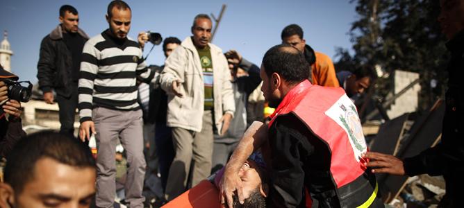 Miembros de la Defensa Civil Palestina sacan de los escombros a un superviviente de un bombardeo israelí en Gaza.