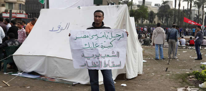 """Un ciudadano egipcio se manifiesta contra Mursi con un cartel que reza: """"Vete Mursi, Egipto es demasiado grande para ti. La gente quiere la caída del régimen""""."""