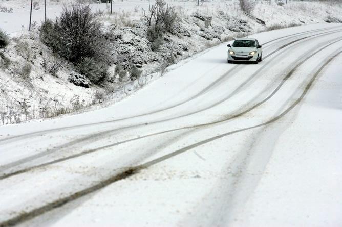Un vehículo circula por una de las carreteras del puerto de San Isidro, en León, durante la nevada registrada en la región.