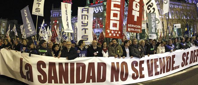 """Pancarta con el lema """"La sanidad no se vende. Se defiende"""" que gran número de personas sostienen a su paso por la plaza de Cibeles"""