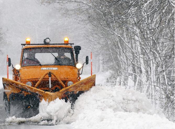 Una pequeña maquina retira la nieve de la calzada para poder acceder al pueblo de Abiada, en Cantabria