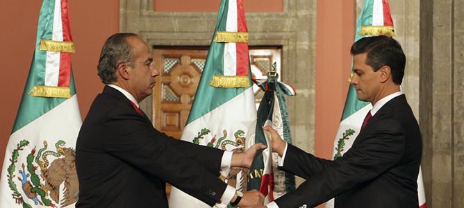 El mandatario saliente, Felipe Calderón, entrega la bandera de México a Peña Nieto, en el acto de investidura del nuevo presidente