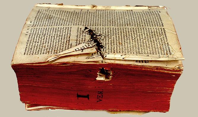 Orificio producido por arma blanca en el lateral, afectando al libro
