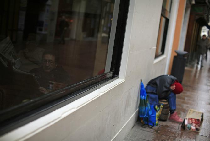 Un hombre lee un periódico en el interior de un bar mientras un mendigo está pidiendo en una calle de Sevilla