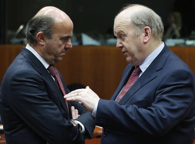 El ministro de Economía español de Guindos saluda al ministro irlandés Noonan durante una reunión en Bruselas