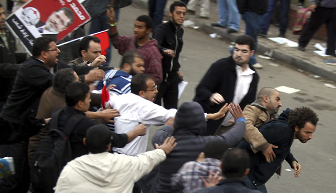 Seguidores del presidente egipcio, Mohamed Mursi, y de los Hermanos Musulmanes, pelean con los opositores que habían acampado frente al Palacio Presidencial de El Cairo
