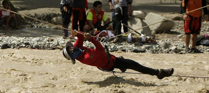 Un miembro de los equipos de rescate utiliza una cuerda para cruzar el agua de las inundaciones durante un rescate en New Bataan, en el Valle de Compostela, al sur de Filipinas.