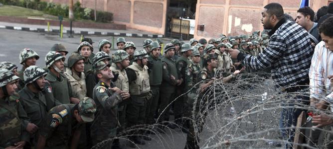 Varias personas se encaran con las fuerzas de seguirdad durante una manifestación en frente del Palacio presidencial de El Cairo.