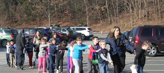 Agentes de seguridad escoltan a alumnos del colegio Sandy Hook (Connecticut) donde se ha perpetrado el tiroteo.