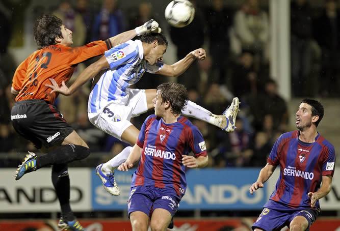El portero del Eibar Joan Altamira despeja un balón ante el defensa brasileño del Málaga Weligton de Oliveira durante el partido de octavos de final de la Copa del Rey que ambos equipos han disputado en el estadio de Ipurua de la localidad guipuzcoana de Eibar
