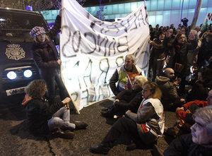 Varios manifestantes protagonizan una sentada durante la protesta organizada por la Mesa en Defensa de la Sanidad Pública contra las medidas sanitarias previstas por la Comunidad de Madrid para 2013, que ha tenido lugar esta tarde ante la Asamblea de Madrid.