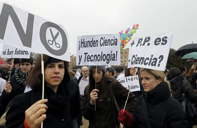 Varios jóvenes sostienen pancartas durante la concentración convocada por el colectivo 'Carta Abierta por la Ciencia', que reúne a sociedades y organizaciones científicas, sindicatos y representantes de la Confederación de Rectores de Universidades Españolas, para exigir un cambio de rumbo en la política