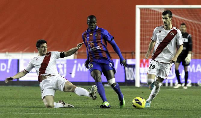 El centrocampista senegalés del Levante Pape Diop pelea un balón con los jugadores del Rayo Vallecano, el centrocampista Javi Fuego, y el delantero brasileño Leo Baptistao, durante el partido de la decimoséptima jornada de liga en Primera División que se disputa esta noche en el estadio de Vallecas