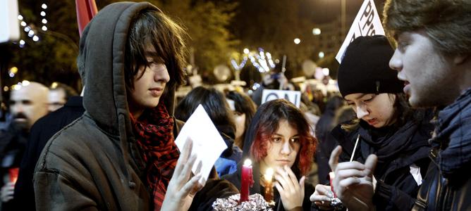 Varios jóvenes portan velas en la manifestación silenciosa convocada frente al Congreso por la coordinadora 25S contra los Presupuestos Generales del Estado.
