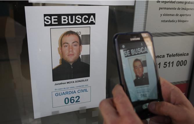 Una persona graba con un móvil uno de los carteles del dispositivo de búsqueda que ha organizado la Guardia Civil para dar con el paradero del supuesto secuestrador de una niña de 16 meses del municipio de Gérgal (Almería)