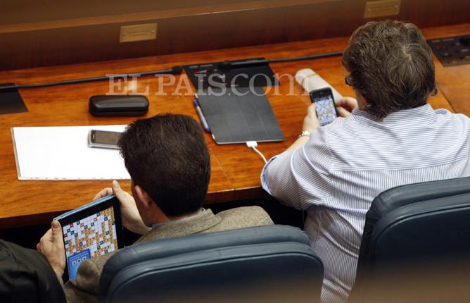 Los diputados del PP Bartolomé González y María Isabel Redondo juegan una partida de Apalabrados durante el pleno en que se ha aprobado, entre otras medidas, la privatización de la gestión de los hospitales públicos madrileños.