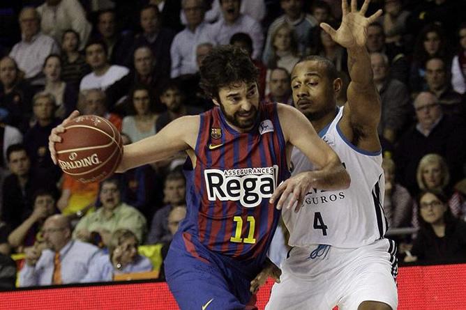 El escolta del F.C. Barcelona Juan Carlos Navarro entra a canasta ante el base estadounidense del Real Madrid Dontaye Draper durante el partido de la decimoquinta jornada de Liga ACB