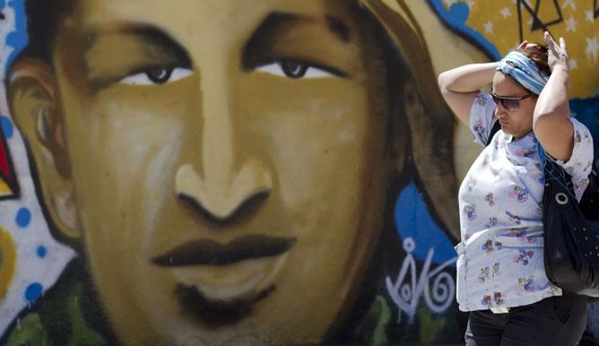 Una mujer pasea frente a un retrato de Hugo Chávez en las calles de Caracas