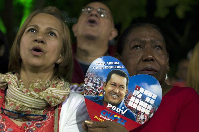 Una seguidora de Hugo Chávez sostiene una fotografía en forma de corazón del presidente durante una de las misas celebradas ayer en Caracas