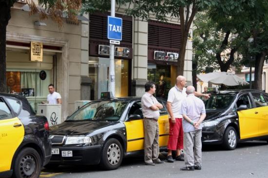 Un grup de taxistes esperen passatge a la parada situada a la cruïlla de Travessera de Gràcia-Bailén