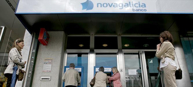 Varias personas esperan para sacar dinero de los cajeros de una sucursal de Novagalicia Banco