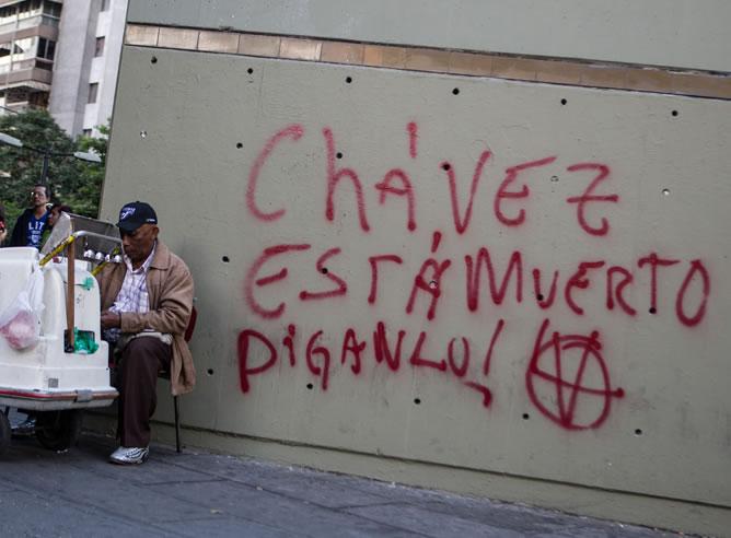 """Un hombre vende helados cerca de un graffiti que especula con la muerte del presidente de Venezuela, Hugo Chávez, en Caracas (Venezuela). El grafiti anuncia: """"Chávez está muerto, diganlo!"""""""