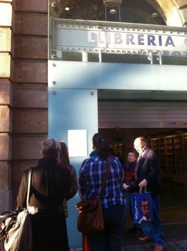 Els vianants s'aturent  a llegir el comunicat que explica les raons del tancament de la llibreria Catalònia