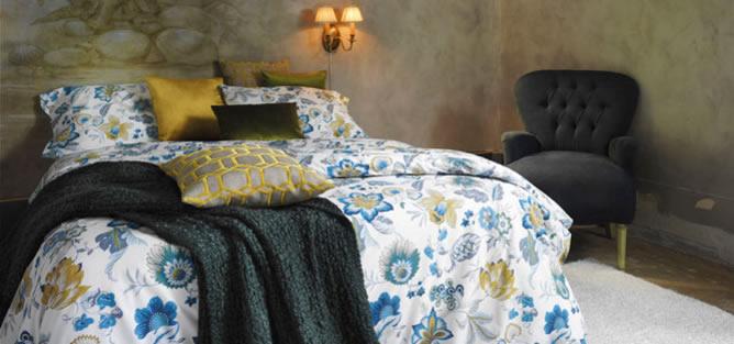 Propuesta de dormitorio con manta sobre la cama y pared de estuco