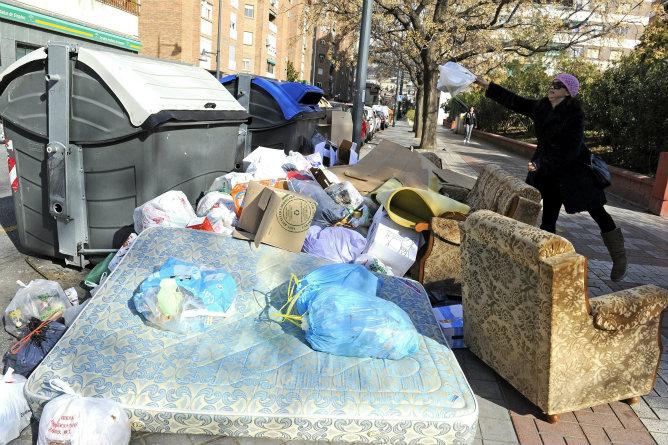Una mujer se dispone a depositar una bolsa de basura junto a varios contenedores que acumulan gran cantidad de residuos, en una calle del centro de Granada